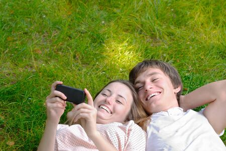 Happy couple laying on the grass make self-photo Stock Photo - 10440442