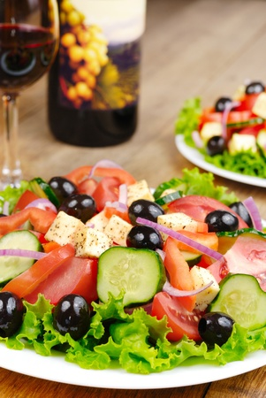 Greek salad and bottle of red wine on the oak table