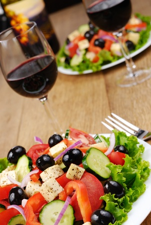 Greek salad and bottle of red wine on the oak table photo