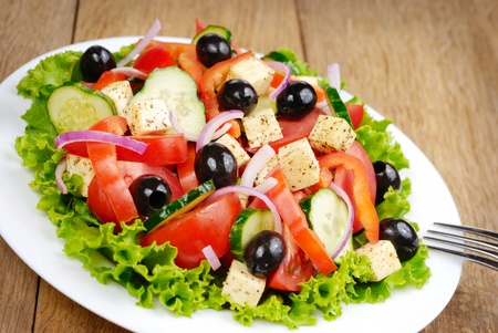Greek salad in the white plate on the kitchen table