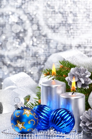 Blue Christmas balls with silver candles over bright background photo
