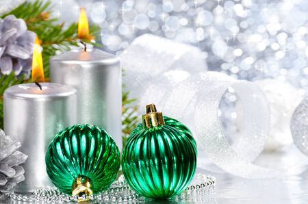 christmas spirit: Christmas balls with silver candles over bright background