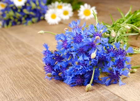 Fresh cornflower and chamomile flowers on the wooden background photo