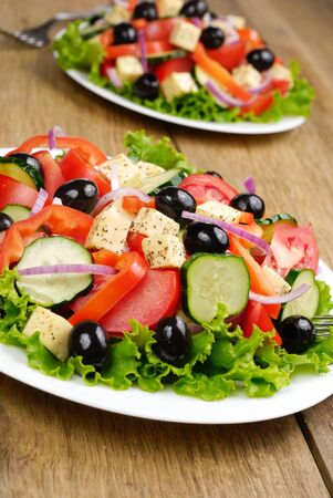 greek salad: Greek salad in the white plate on the kitchen table