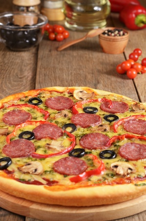 Pepperoni pizza with mushrooms and paprica on the kitchen table with spices photo