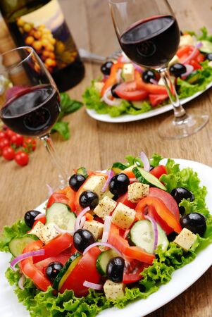 Greek salad and glass of red wine on the kitchen table photo