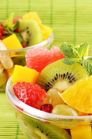 Healthy fruit salad over green background closeup photo