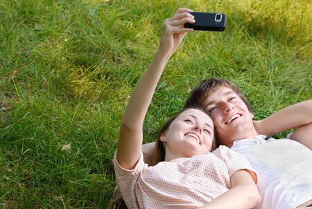 Happy couple laying on the grass watching at smart-phone photo