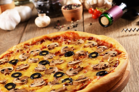 melted cheese: Pizza with mushrooms on the kitchen table along with spices and wine bottle Stock Photo
