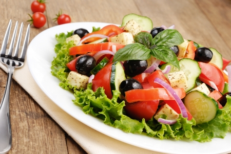 Greek salad served on the oak table