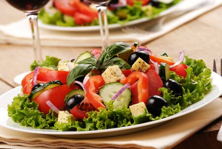 Greek salad and glasses of red wine on the oak table photo