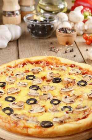 Pizza with mushrooms on the kitchen table along with spices photo