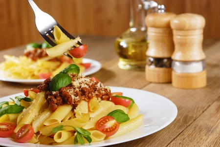 Rigatoni pasta with a tomato beef sauce on the oak table photo