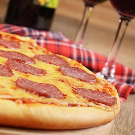 Pepperoni pizza along with wineglasses and bottle photo
