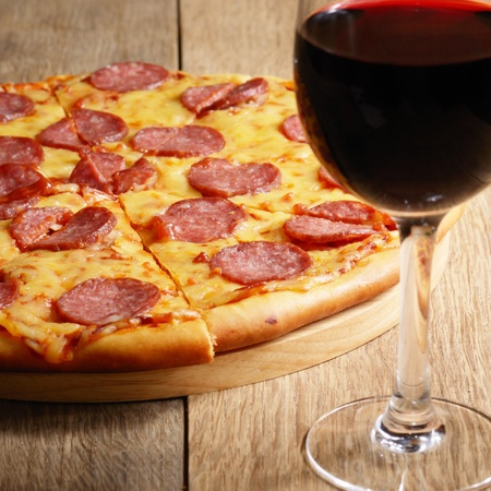 Pepperoni pizza along with wineglass photo
