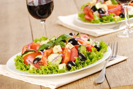 Greek salad and glasses of red wine photo