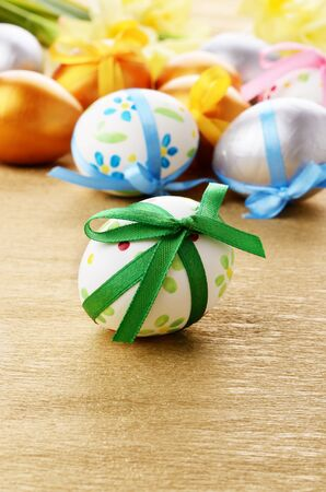Easter eggs with bows on gold over floral background Stock Photo - 12585438
