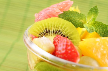 Healthy fruit salad over green background photo