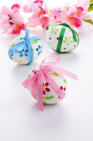 Easter eggs with flowers over white photo