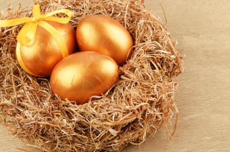 Golden Easter eggs in the nest over gold background photo