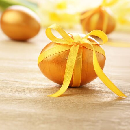 Easter eggs with bows on gold over floral background photo