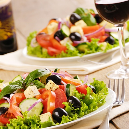 Greek salad and glass of red wine on the oak table photo
