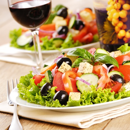 Greek salad and glass of red wine on the oak table Stock Photo