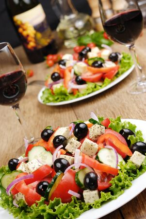 Greek salad and glass of red wine on the oak table Stock Photo - 13219817