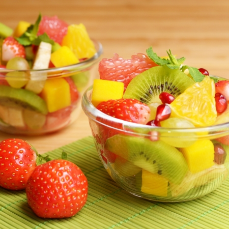 fruits background: Healthy fruit salad in the glass bowls