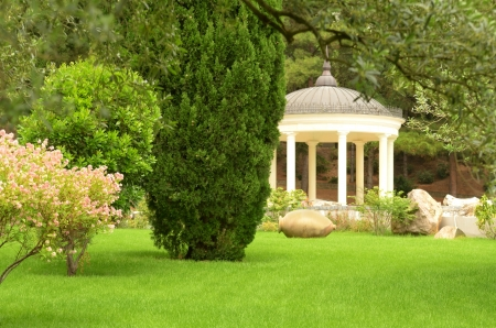 White stone gazebo in the green summer park