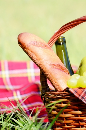 Picnic basket with red napkin fool of fruits, bread and wine on green grass photo