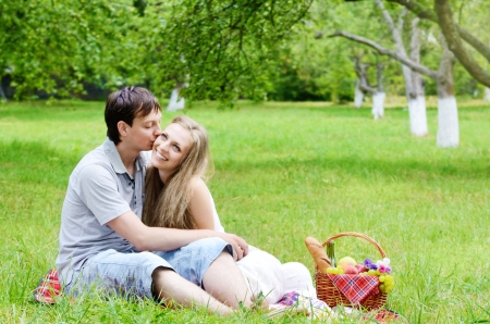 Young happy couple in love having fun at picnic outdoors photo