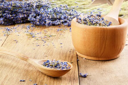 Pestle and mortar with lavender flowers on the oak table  photo