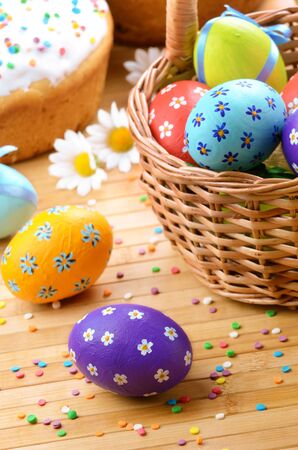 Easter decorations - eggs, cake and basket on the tabletop photo
