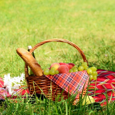 Picnic basket with red napkin fool of fruits, bread and wine Stock Photo