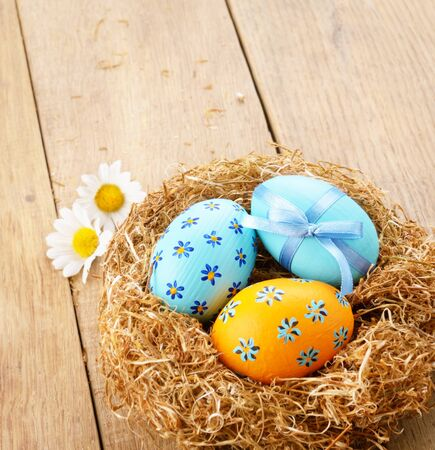 Nest with Easter eggs on the wooden table with copy-space photo