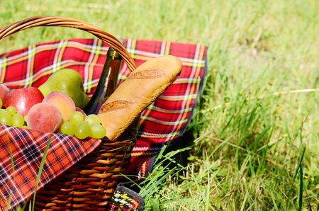 family picnic: Picnic basket with red napkin fool of fruits, bread and wine with copy-space Stock Photo