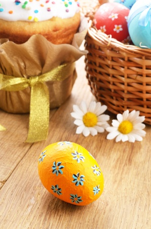 Easter decorations - eggs, cake and basket on the tabletop Stock Photo - 15348150