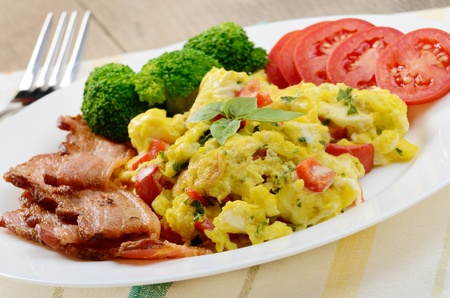 Scrambled eggs with fried bacon on the white plate photo