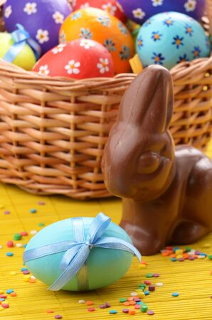 Easter eggs, cake, basket and bunny shape chocolate photo