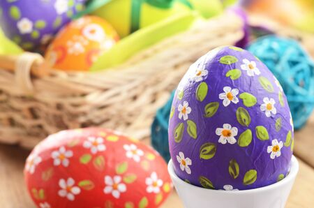 Hand crafted easter eggs with wicker basket photo