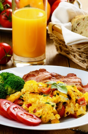 Omelet with vegetables, fried bacon and orange juice photo