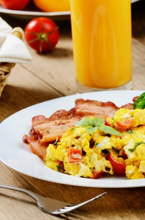 Omelet with vegetables, fried bacon and orange juice