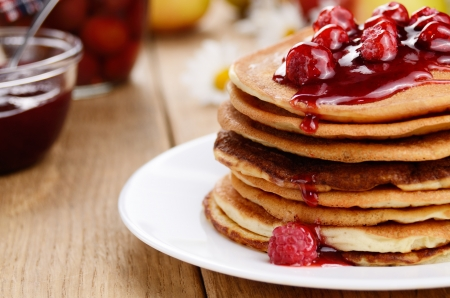 Delicious pancakes with raspberries on the wooden kitchen table photo