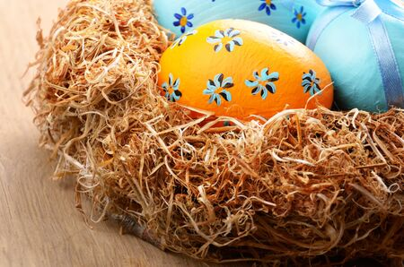 religious event: Nest with Easter eggs on the wooden table