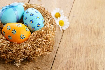 Nest with Easter eggs on the wooden table photo