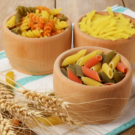 Raw tricolor pasta set on the wooden table photo