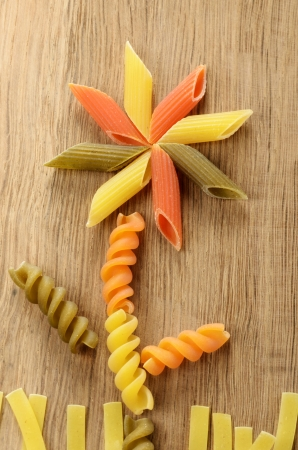 penne: Pasta concept with flower on the wooden table Stock Photo