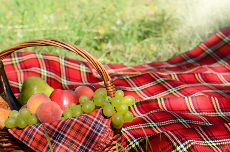 Picnic basket with red napkin fool of fruits, bread and wine photo