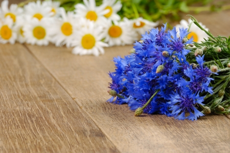 Fresh cornflower and chamomile flowers on the wooden desktop photo